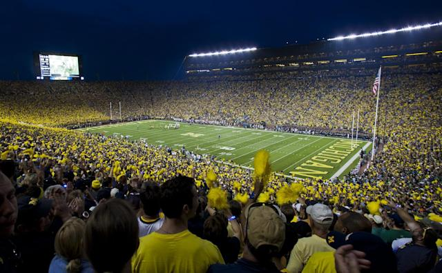 Fans cheer on Michigan and Notre Dame as they begin an NCAA college football game, in Ann Arbor, Mich., Saturday, Sept. 7, 2013. This is only the second ever night game played at Michigan Stadium. (AP Photo/Tony Ding)