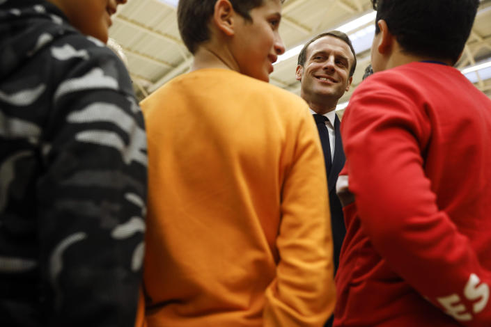 """French President Emmanuel Macron, talks with youths during his visit in Mulhouse, eastern France, Tuesday, Feb. 18, 2020. Macron said Tuesday he was determined to fight against """"Islamist separatism"""" but also """"discrimination ». (AP Photo/Jean-Francois Badias, Pool)"""