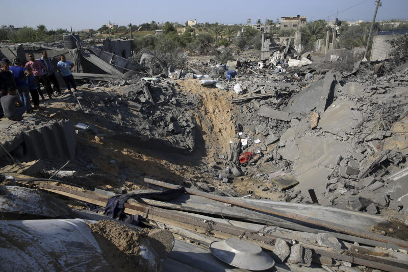 Palestinians inspect a crater and the rubble of destroyed houses following overnight Israeli missile strikes, in Al-Qarara, east of Khan Younis, southern Gaza Strip, Thursday, Nov. 14, 2019. (AP Photo/Adel Hana)