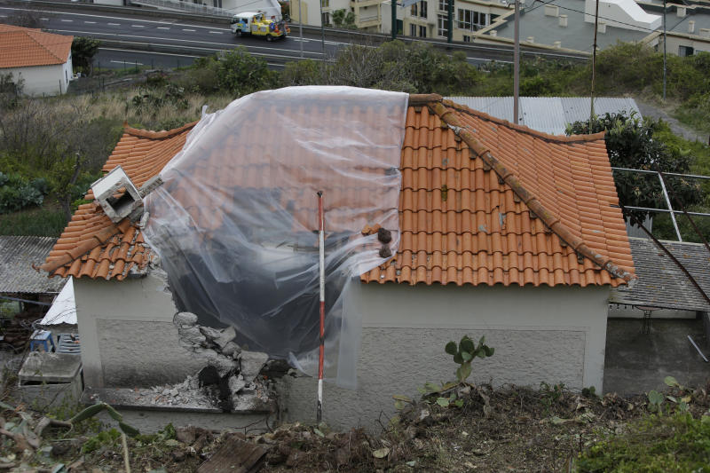 A hole in the damaged house that a tourist bus crashed into after veering off the road killing 29 people is covered with a plastic sheet in Funchal, the capital of Portugal's Madeira Island, Friday April 19, 2019. A German plane is expected to arrive Friday in Madeira to take home survivors from the bus accident that killed 29 tourists after it veered off the road and plunged down a slope. All the deceased were German. The bus carried 55 people, including a Portuguese driver and guide. Sixteen people remain hospitalized, but authorities said all of them are out of danger. (AP Photo/Armando Franca)