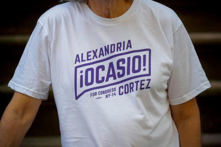 Peter Hogness poses wearing his Alexandria Ocasio-Cortez branded T-shirt in the Park Slope area of Brooklyn, New York