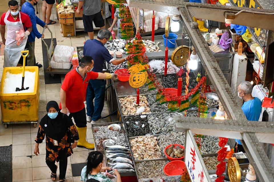 Vendors arranging seafood at a wet market in Singapore on 6 January. (PHOTO: Getty Images)