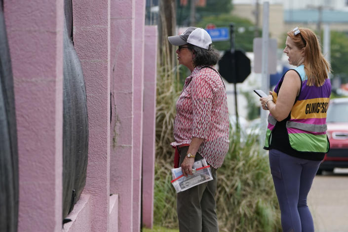 """Pam Miller, an anti-abortion sidewalk counselor, left, speaks through the tarp draped fencing of the Jackson Womens Health Organization clinic, to an incoming patient at the front of the """"pink house,"""" while clinic escort Kim Gibson counters her statements, Thursday, May 20, 2021, in Jackson, Miss. The clinic is Mississippi's only state licensed abortion facility. On May 17, 2021, the U.S. Supreme Court agreed to take up the dispute over a Mississippi ban on abortions after 15 weeks of pregnancy. The issue is the first test of limits on abortion access to go before the conservative majority high court. Their decision could mean more restrictions, and focuses on the landmark 1973 ruling in Roe v. Wade, which established a woman's right to an abortion. (AP Photo/Rogelio V. Solis)"""