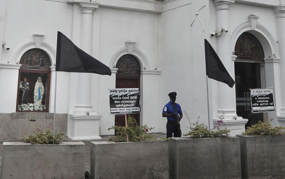 A policeman stands guard as black flags are seen in front of St. Anthoney's Church, in Colombo, Sri Lanka, Saturday, Aug. 21, 2021. Sri Lankan Catholics hoisted black flags in churches and at homes on Saturday protesting against what they call government's inaction to find the true conspirators in the Easter Sunday blasts of 2019 which killed 269 people. (AP Photo/Eranga Jayawardena)