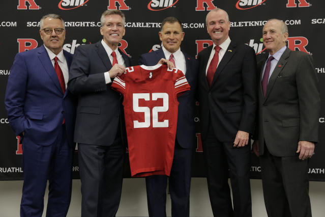 New Rutgers NCAA college football head coach Greg Schiano, center, poses for a picture with Greg Brown, chairman of the Committee on Intercollegiate Athletics, left, Rutgers athletic director Pat Hobbs, second from left, New Jersey Gov. Phil Murphy, second from right, and Rutgers president Robert Barchi, right, after an introductory news conference in Piscataway, N.J., Wednesday, Dec. 4, 2019. After an on-again, off-again courtship, Schiano is back as Rutgers football coach. (AP Photo/Seth Wenig)