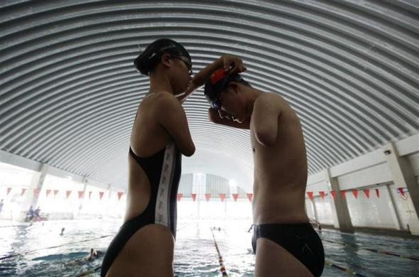 Yang Ping (L), 22, from the Yunzhinan Swimming Club for the handicapped, puts on swimming goggle for her teammate Xu Qing, 20, during a daily training session at a swimming centre in Kunming, southwest China's Yunnan province, July 30, 2011.