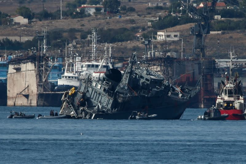 The damaged Hellenic Navy minehunter HS Kallisto is towed after its collision with a container ship off the port of Piraeus, near Perama