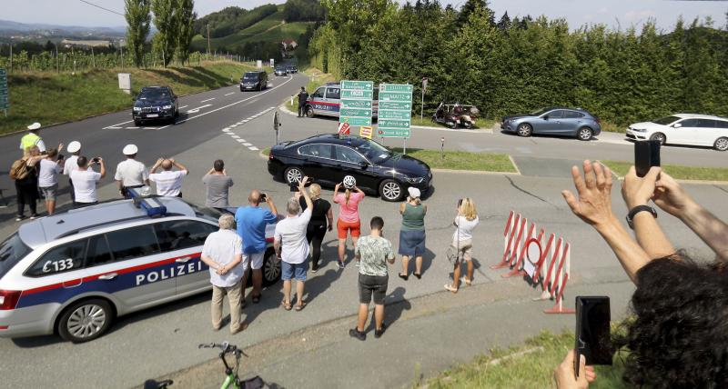People attend the arrival of the car convoy of Russia's President Vladimir Putin on its way for the wedding of Austria's Foreign Minister Karin Kneissl and Wolfgang Meilinger in Sulztal an der Weinstrasse, Austria, Saturday, Aug. 18, 2018. (AP Photo/Ronald Zak)