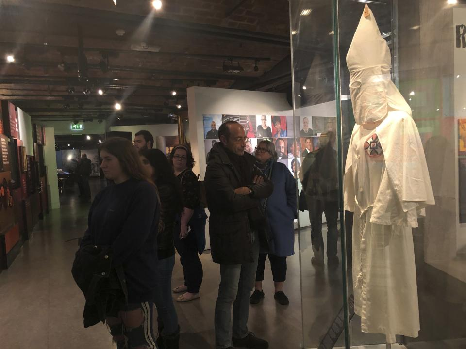 In this Nov. 24, 2019 photo, visitors at the International Slavery Museum in Liverpool, England, examine a display of a 1920s-era Ku Klux Klan outfit from Port Jervis, N.Y. The museum seeks to tell the story of the enslavement of people from Africa and how the British city benefited from human bondage. (AP Photo/Russell Contreras)