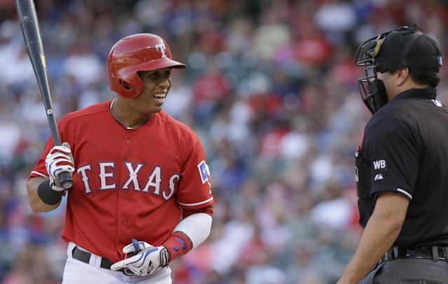 Texas Rangers Leonys Martin, left, reacts to a strike three call by home plate umpire Jim Reynolds ending the first inning of a baseball game against the Los Angeles Angels in Arlington, Texas, Saturday, July 12, 2014. (AP Photo/LM Otero)