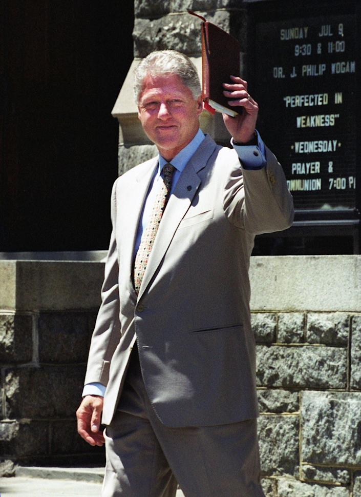 President Bill Clinton waves his Bible following a church service at Foundry United Methodist Church on July 9, 2000, in Washington, D.C.