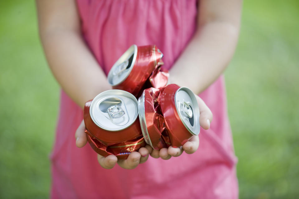 Hands hold crushed soft drink cans. Source Getty Images