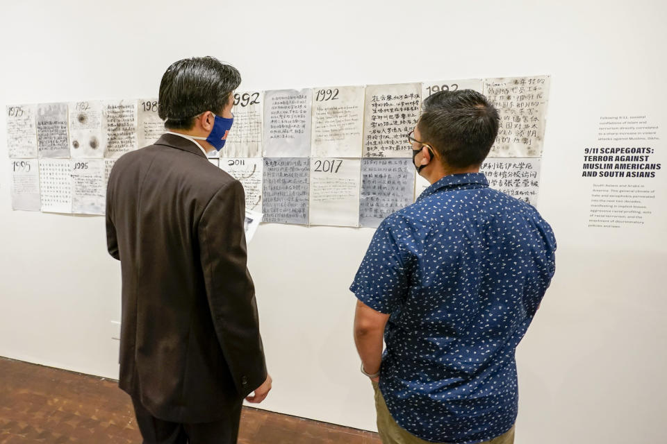 """Visitors inspect the exhibit during the press preview of """"Responses: Asian American Voices Resisting the Tides of Racism"""" at the Museum of Chinese in America, Wednesday, July 14, 2021, in New York. (AP Photo/Mary Altaffer)"""