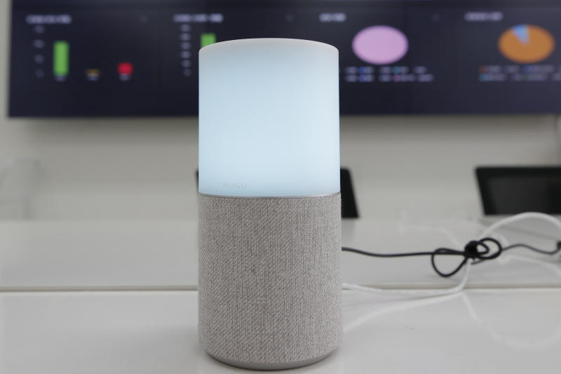 """SK Telecom's AI speaker Nugu built with an artificial intelligence called """"Aria"""" and a lamp that turns blue when processing voice commands for news, music and internet searches, is seen in Seoul, South Korea, on May 13, 2020. The devices can also use quizzes to monitor the memory and cognitive functions of their elderly users, which would be potentially useful for advising treatments. (AP Photo/Lee Jin-man)"""
