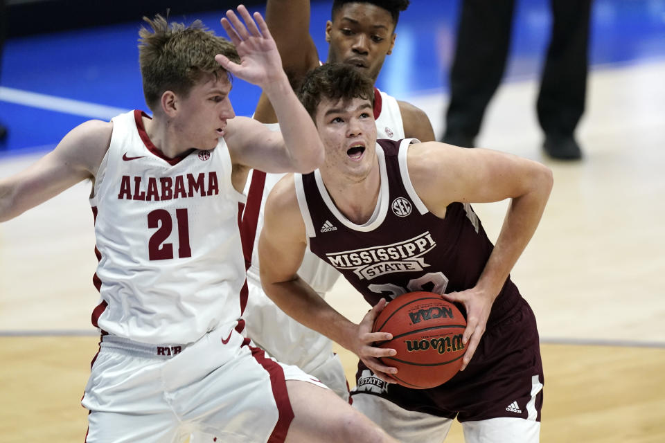 Mississippi State's Quinten Post (32) grabs a rebound next to Alabama's Britton Johnson (21) in the second half of an NCAA college basketball game in the Southeastern Conference Tournament Friday, March 12, 2021, in Nashville, Tenn. (AP Photo/Mark Humphrey)