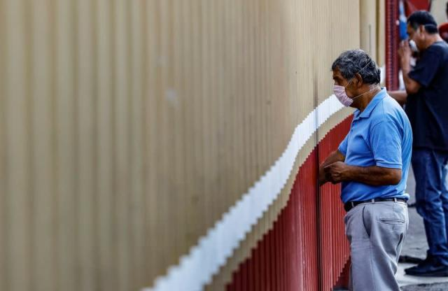 A man stands behind a fence of the triage for the coronavirus disease (COVID-19) patients as the spread of COVID-19 continues in Mexico City