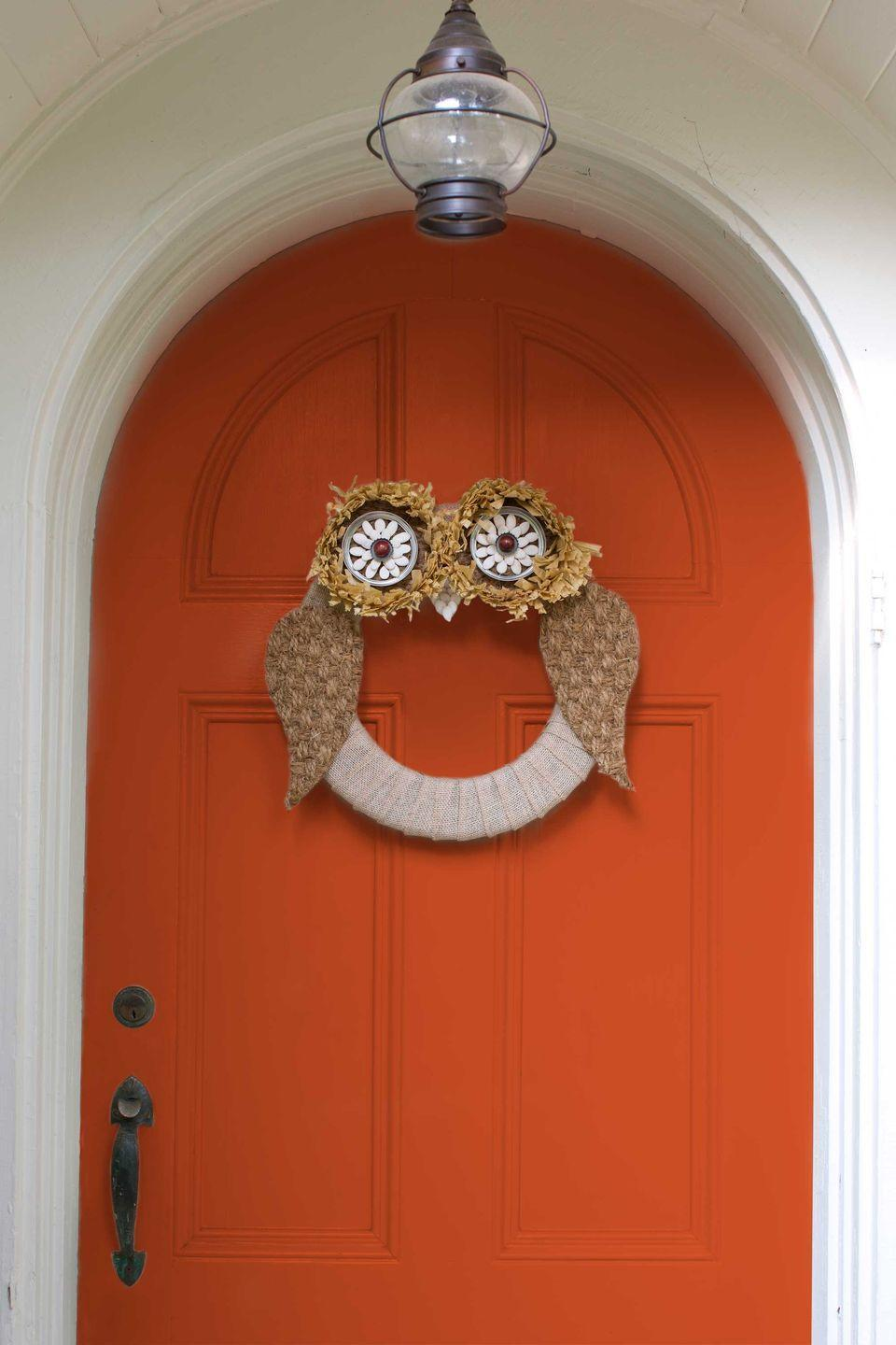 """<p>Fashion this owl wreath for an adorable fall entrance. Your neighbors will think it's a hoot! Wrap burlap ribbon around a 12"""" Styrofoam form. For the eyes, use utility scissors to cut a 5"""" circle from a sisal doormat. Trim a 2"""" strip from the edge of a raffia table skirt and hot-glue along the outer edge.</p><p>Next, hot-glue the outer ring of a 41/2""""-inch Mason jar lid inside the raffia, securing it to the sisal circle. Hot-glue a metal bottle cap at the center of the ring and encircle with dried pumpkin seeds. Hot-glue a red wood bead inside bottle cap. Repeat for second eye. For the wings, cut two 8""""H x 5""""W teardrop-shaped pieces from the doormat. For the beak, cut a 3"""" triangle from the mat; cover with dried pumpkin seeds. Attach the beak, then the eyes and wings, with hot-glue.</p>"""