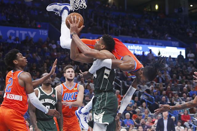 Oklahoma City Thunder forward Nerlens Noel falls over Milwaukee Bucks forward Giannis Antetokounmpo during the second half of an NBA basketball game Sunday, Nov. 10, 2019, in Oklahoma City. (AP Photo/Sue Ogrocki)