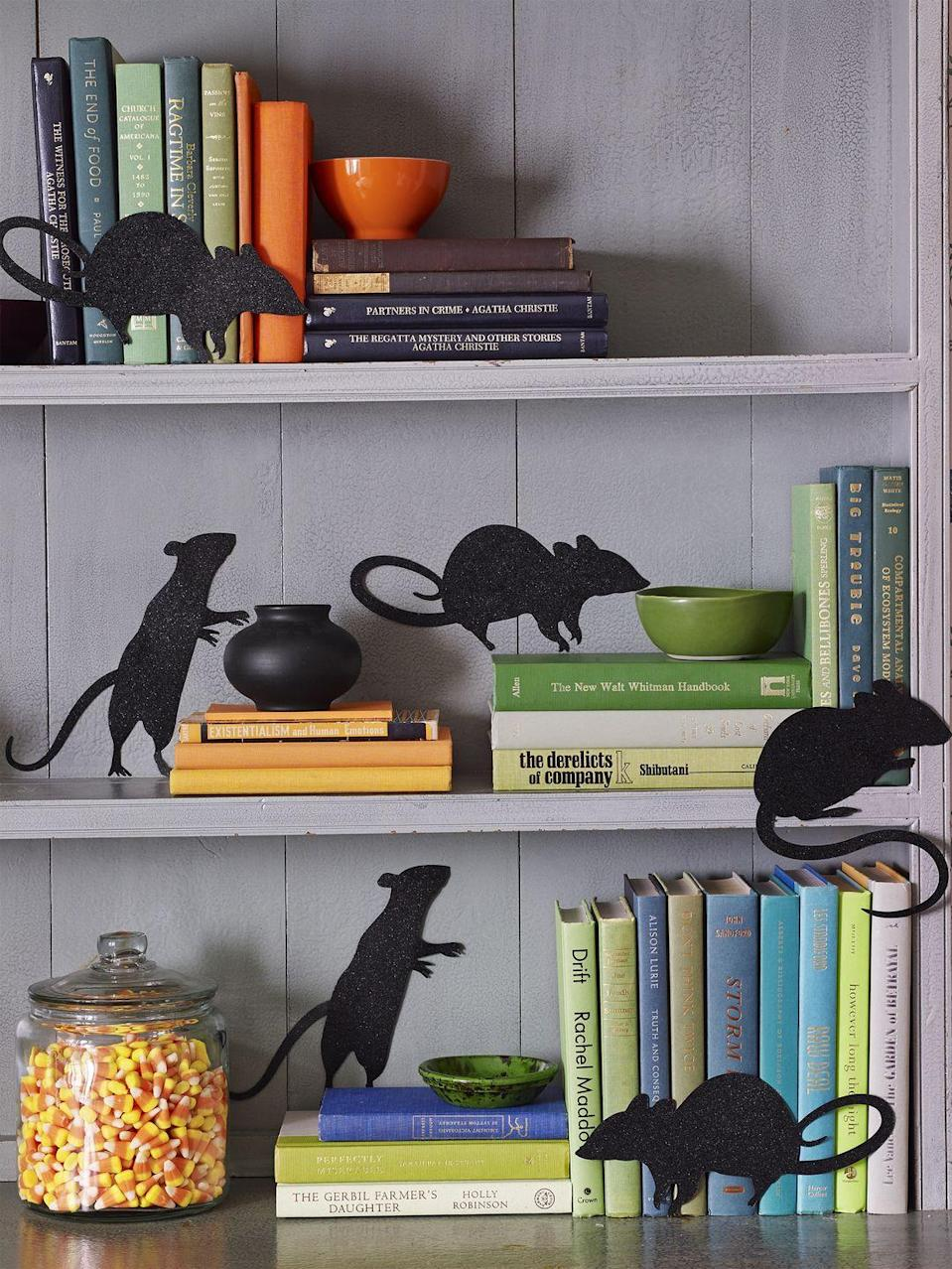 """<p>A stack of books is the perfect hiding place for (paper) mice. Print out silhouettes and trace onto black cardstock for extra-lifelike rodents. </p><p><em><a href=""""https://www.womansday.com/home/decorating/g1279/easy-halloween-decorations/"""" rel=""""nofollow noopener"""" target=""""_blank"""" data-ylk=""""slk:Get the tutorial at Woman's Day »"""" class=""""link rapid-noclick-resp"""">Get the tutorial at Woman's Day »</a></em> </p>"""