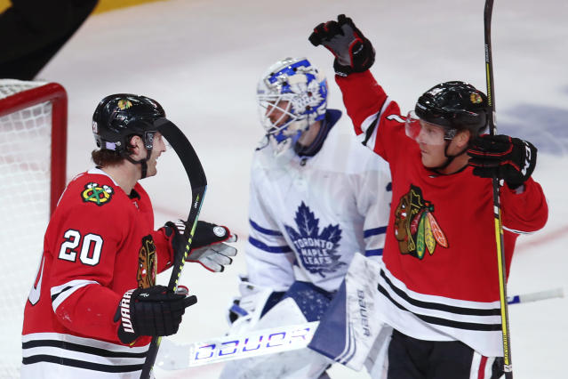 Chicago Blackhawks' Brandon Saad, left, celebrates his goal on Toronto Maple Leafs' Michael Hutchinson, center, with Drake Caggiula during the third period of an NHL hockey game Sunday, Nov. 10, 2019, in Chicago. (AP Photo/Jim Young)