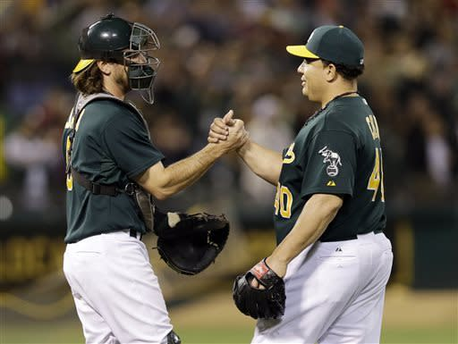 Oakland Athletics starting pitcher Bartolo Colon, left, celebrates with catcher John Jaso after pitching a complete-game shutout against the Chicago White Sox during a baseball game on Friday, May 31, 2013, in Oakland, Calif. Oakland won 3-0. (AP Photo/Marcio Jose Sanchez)