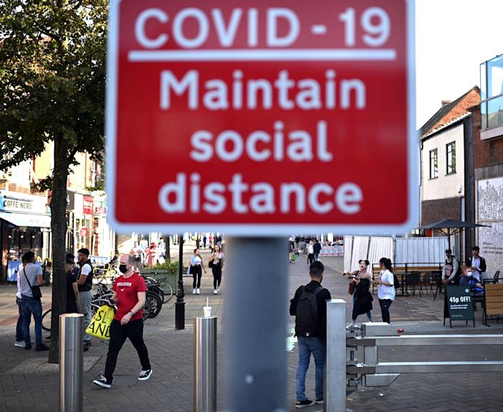 People walk past a sign encouraging social distance in a shopping street in Solihull. (Getty)