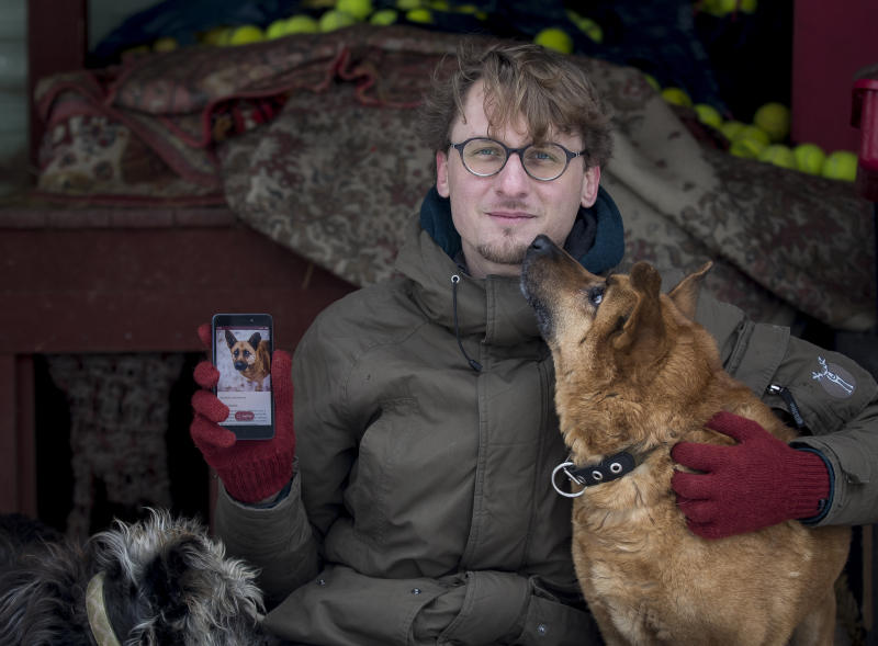 In this photo taken on Saturday, Feb. 2, 2019, Vaidas Gecevicius, who developed an app helping to match stray dogs with potential owners, poses for a picture with a dog and shows this dog's profile on the app in Vilnius, Lithuania. A group of enthusiasts have launched an app that helps match aspiring dog owners with stray dogs. (AP Photo/Mindaugas Kulbis)