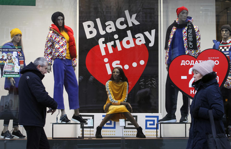 People walk past a shop window with Black Friday advertising on the Khreshchatyk street in center of Kyiv, Ukraine, on 27 November, 2019. Black Friday is a friday after Thanksgiving in the US, which begins with the traditional Christmas season of sales. (Photo by STR/NurPhoto via Getty Images)