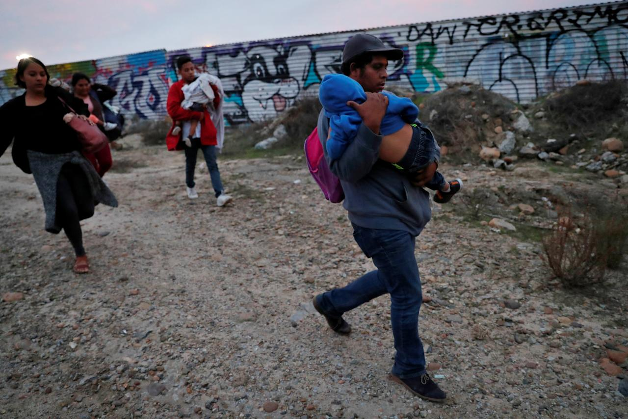 A migrant child sleeps while he is carried by family as fellow migrants, all part of the caravan of migrants who traveled from Central America with the intention of crossing into the U.S., walk to the border fence in order to cross into the U.S. from Tijuana, Mexico December 14, 2018. REUTERS/Leah Millis