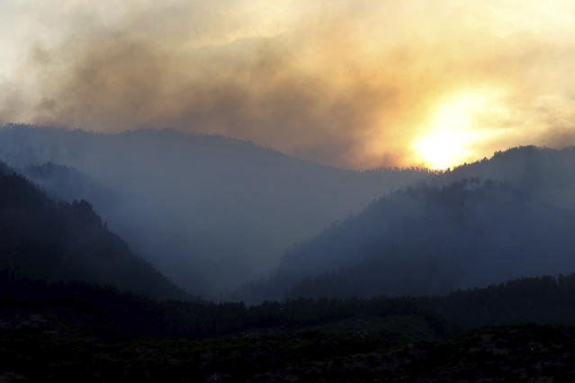 <p>As the sun sets, smoke rises from a 416 Fire burn area west of the Falls creek Ranch subdivision late Wednesday, June 13, 2018, near Durango, Colo. (Photo: Jerry McBride/The Durango Herald via AP) </p>