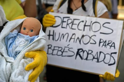 """Demonstrators hold placards reading """"human rights for stolen babies"""" on the opening day of the first trial in Madrid over thousands of suspected cases of babies stolen from their mothers during the Franco era"""