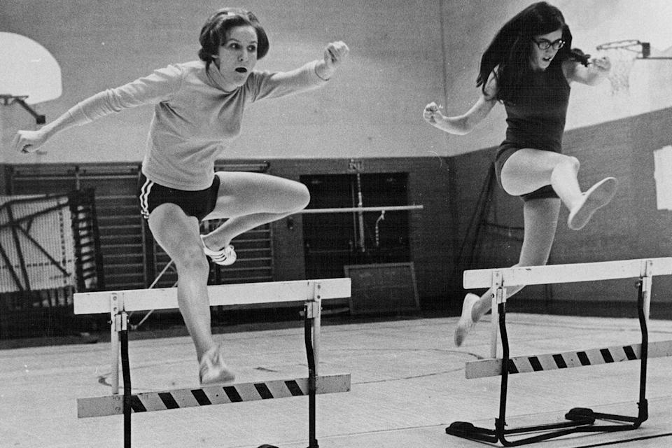 <p>Two high schoolers attempt to conquer a few hurdles during gym class.</p>
