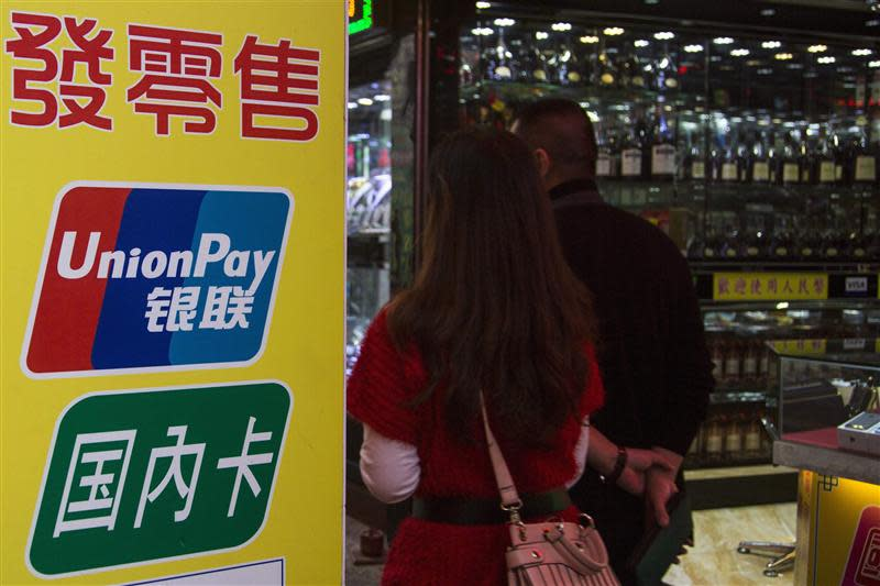 File photo of Chinese visitors walking past a sign for China UnionPay outside a pawnshop in Macau