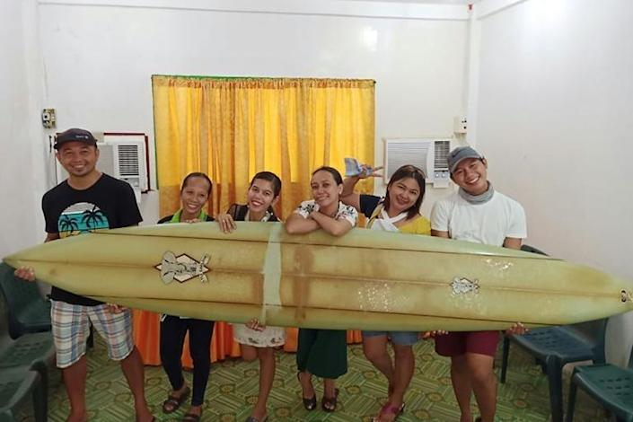 Filipino teacher Giovanne Branzuela (L) poses with the surfboard, once owned by big wave surfer Doug Falter who lost it while surfing in Hawaii two years