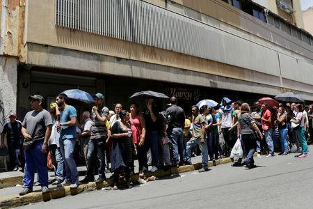 People queue to try to buy basic food items outside a supermarket in Caracas, Venezuela, April 28, 2016. REUTERS/Marco Bello/File Photo