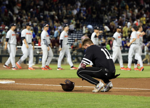 Mississippi State's Jordan Westburg squats near the baseline as Oregon State players celebrate following an NCAA College World Series baseball elimination game in Omaha, Neb., Saturday, June 23, 2018. Oregon State won 5-2. (AP Photo/Nati Harnik)