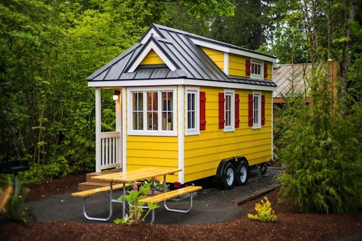 """<p>Just one of the homes in Oregon's Mt. Hood Tiny House Village, """"Savannah"""" features yellow cedar plank siding with red shutters and white trim. So welcoming!</p><p><a class=""""link rapid-noclick-resp"""" href=""""https://go.redirectingat.com?id=74968X1596630&url=https%3A%2F%2Fwww.tripadvisor.com%2FShowUserReviews-g52127-d909607-r464373430-Mt_Hood_Village_RV_Resort-Welches_Clackamas_County_Oregon.html&sref=https%3A%2F%2Fwww.oprahdaily.com%2Flife%2Fg35047961%2Ftiny-house%2F"""" rel=""""nofollow noopener"""" target=""""_blank"""" data-ylk=""""slk:PLAN YOUR TRIP"""">PLAN YOUR TRIP</a> <a class=""""link rapid-noclick-resp"""" href=""""https://www.countryliving.com/life/travel/g3595/tour-tiny-house-village/"""" rel=""""nofollow noopener"""" target=""""_blank"""" data-ylk=""""slk:SEE INSIDE"""">SEE INSIDE</a><br></p>"""