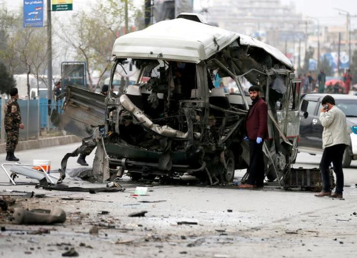 FILE PHOTO: Afghan officials inspect a damaged minibus after a blast in Kabul