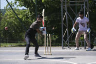 A batter prepares to play a shot during a game of cricket played by migrants in Tuzla, Bosnia, Friday, May 21, 2021. The Rome-based Baobab Experience group brought cricket equipment for the migrants in the Bosnian capital of Sarajevo and the central town of Tuzla, offering a rare opportunity for relaxation and fun for the people who spend months, if not years, stuck in camps while fleeing war and poverty in their nations and chasing their dreams of a better future. (AP Photo/Kemal Softic)