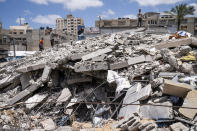 People stand atop a debris pile as they gather reclaimable items from the site of a building previously destroyed by an air-strike prior to a cease-fire reached after an 11-day war between Gaza's Hamas rulers and Israel, in Gaza City, Saturday, May 22, 2021. (AP Photo/John Minchillo)
