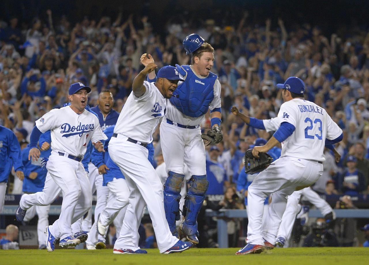 Los Angeles Dodgers celebrate a 4-3 win over the Atlanta Braves in Game 4 in the National League baseball division series Monday, Oct. 7, 2013, in Los Angeles. The win sends the Dodgers to the NL championship series. (AP Photo/Mark J. Terrill)