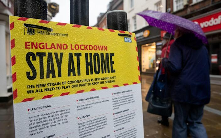 People walk past a Government sign warning people to stay at home on the High street in Winchester, Hampshire - Andrew Matthews/PA Wire