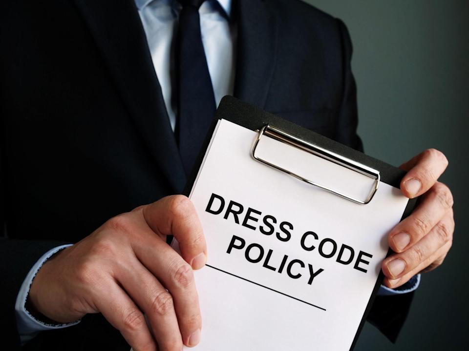 """Man holding a clipboard reading """"dress code policy"""""""
