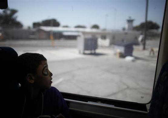 A boy looks out of the bus window as he leaves his mother at California Institute for Women state prison in Chino, California May 5, 2012. An annual Mother's Day event, Get On The Bus, brings children in California to visit their mothers in prison. Sixty percent of parents in state prison report being held over 100 miles from their children.
