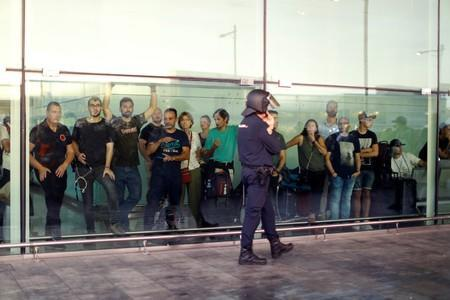 Passengers look as a police officer walks past at Barcelona's airport, during a protest after a verdict in a trial over a banned independence referendum