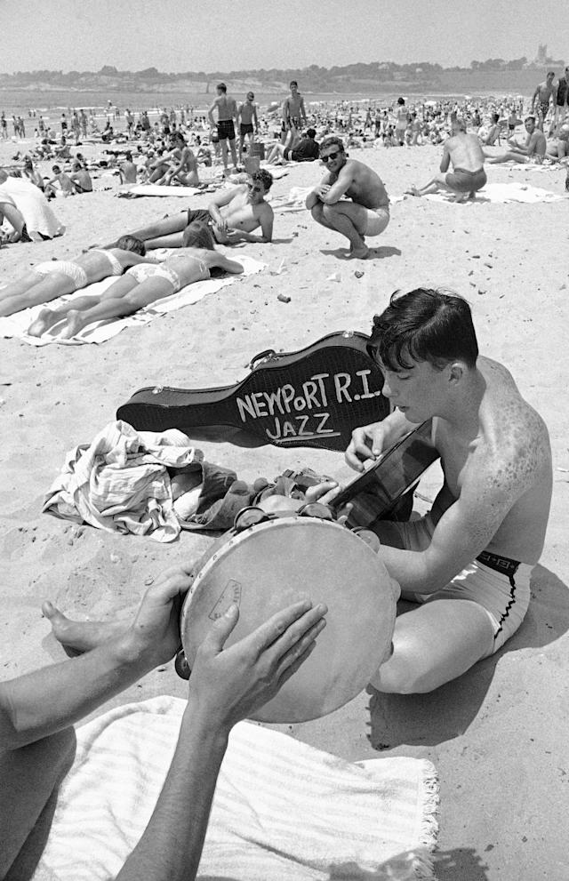 <p>With the temperatures soaring into the 90s, thousands of people who are attending the annual Newport Jazz Festival have headed for the city's beaches. Apparently the music also goes to the beach with the jazz fans. Bob Cross, 21, Pawtucket, R.I., strums his guitar along with other amateur musicians in Newport, R.I., on July 4, 1966. (Photo: Bob Daugherty/AP) </p>