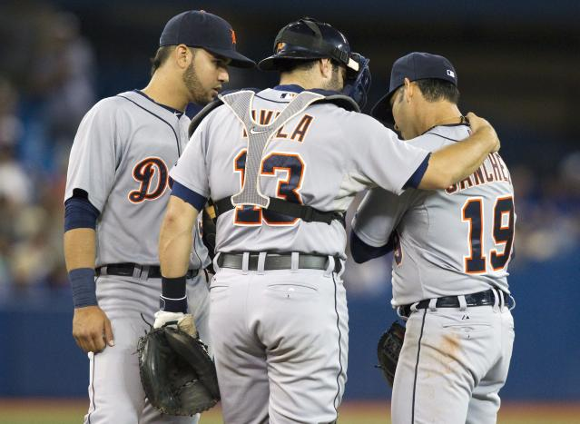Detroit Tigers catcher Alex Avila and Nick Castellanos talk to pitcher Anibal Sanchez, right, on the mound as he favors his pitching arm during the fifth inning of a baseball game, Friday, Aug. 8, 2014 in Toronto. (AP Photo/The Canadian Press, Fred Thornhill)