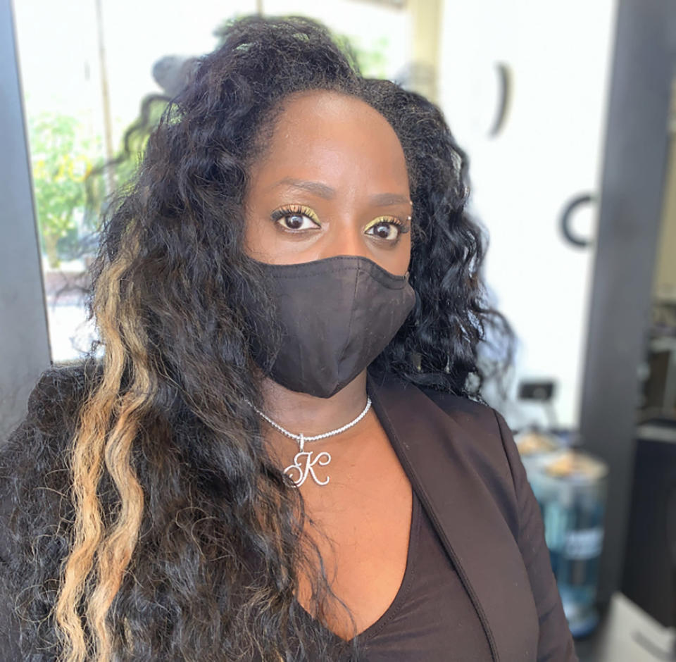 """Boston salon owner Kanessa Alexander says this photo of her wearing a mask in her salon on July 20, 2020, tells the story of her year. """"I was in the salon alone with a mask on during lockdown, when we were closed. It was such an uncertain and uncomfortable time,"""" she said. """"It was a summer day and it should have been a day that I was at the beach with my kids or in the salon with a full staff working."""" Instead, she's seen her staff dwindle from eight to one. (Kanessa Alexander via AP)"""