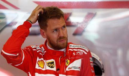 Formula One - F1 - Australian Grand Prix - Melbourne, Australia - 24/03/2017 Ferrari driver Sebastian Vettel of Germany scratches his head in the team garage during the first practice session.  REUTERS/Brandon Malone