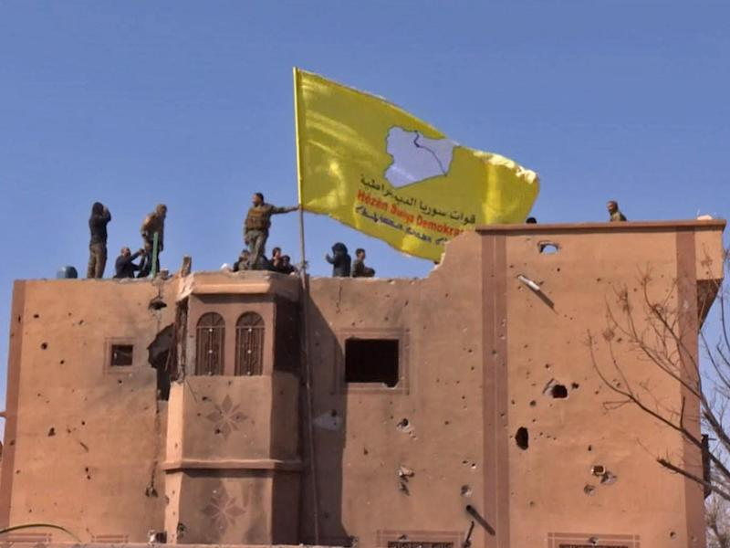 An image grab released by the Kurdish Ronahi TV shows the Syrian Democratic Forces (SDF) raising their flag atop a building (AFP/Getty Images)
